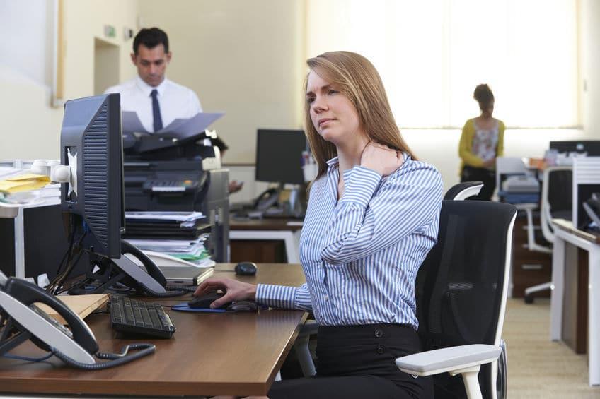 vrouw op niet passende bureaustoel. Stoel is veel te breed en armleggers staan te ver naar voren.